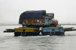 A truck loaded with paddy crop is transported through the waters of river Brahmaputra (Photo: Reuters)