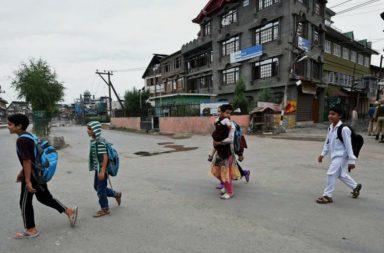 Children with school bags crossing a road in Srinagar. (Photo: PTI)