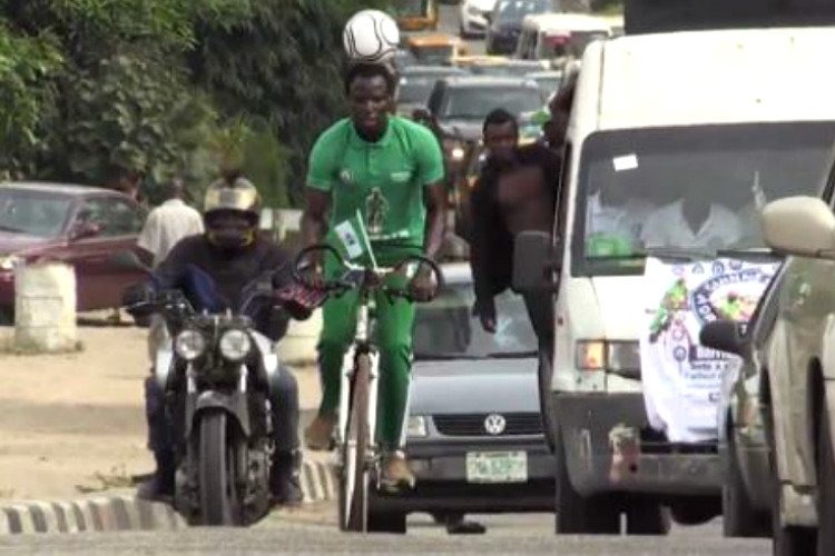 Can you cycle for 100 km while balancing a football on yourhead?