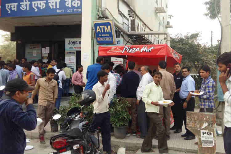 Standing in long queue at ATMs without food? Enjoy pan pizza free of cost