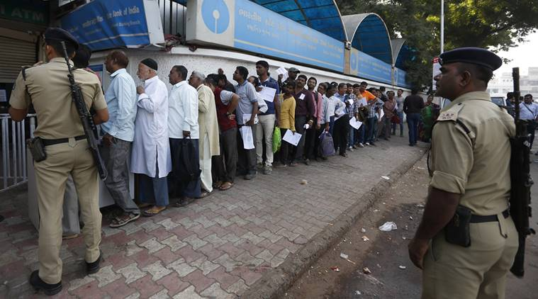 Indian policemen stand guard as people queue up outside a bank to exchange and deposit Indian currency of rupees 500 and 1000 denominations in Ahmadabad, India, Thursday, Nov. 10, 2016. Delivering one of India's biggest-ever economic upsets, Prime Minister Narendra Modi this week declared the bulk of Indian currency notes no longer held any value and told anyone holding those bills to take them to banks. (AP Photo/Ajit Solanki)