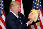 Donald Trump looks at a mask of himself (Photo: Reuters/Carlo Allegri)