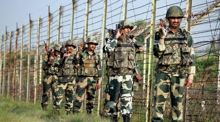 Border Security Force (BSF) personnel patrol along the fence at International Border in RS Pura Sector, Jammu