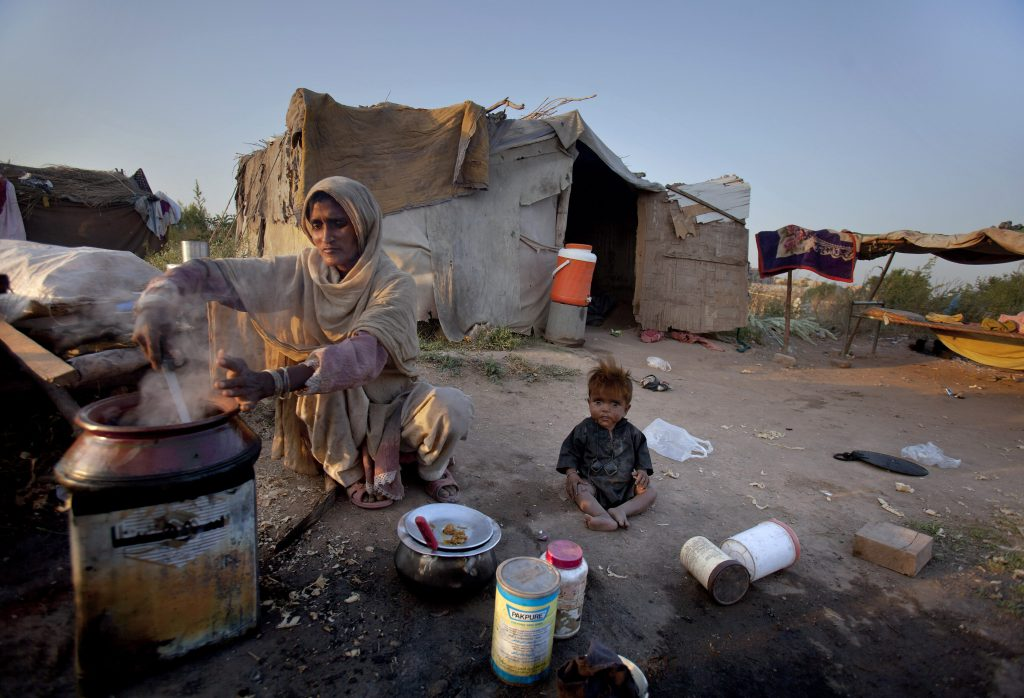 A Pakistani woman prepares food as her child plays on the ground outside their shanty on International Day for Eradication of Poverty at a slum in Islamabad, Pakistan on Monday, Oct. 17, 2011. Pakistan is facing high poverty rate, with a majority of people living below the poverty line. (AP Photo/Anjum Naveed)