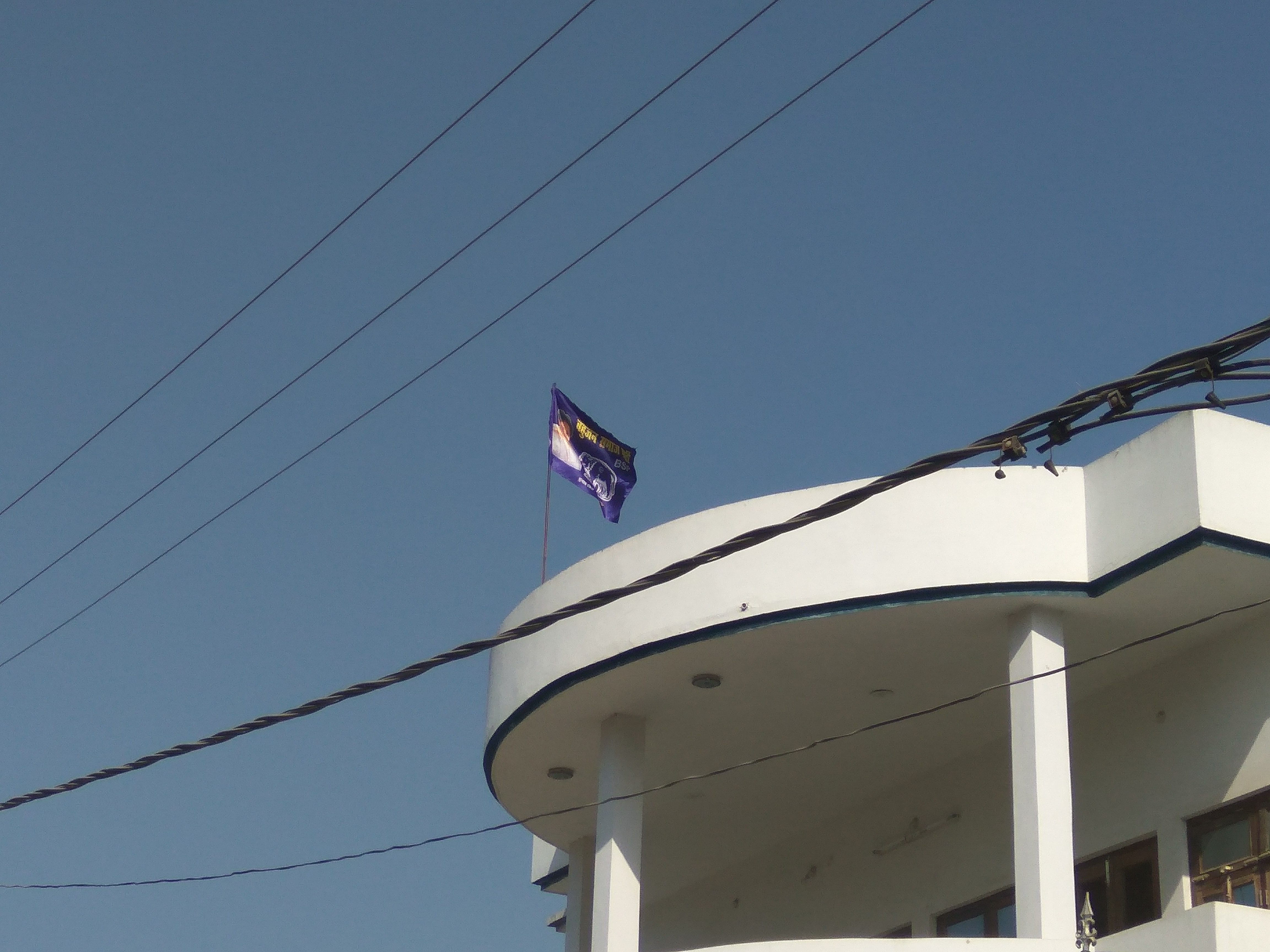 A BSP flag with former CM Mayawati's picture soaring high at a rooftop in Ambedkar Nagar