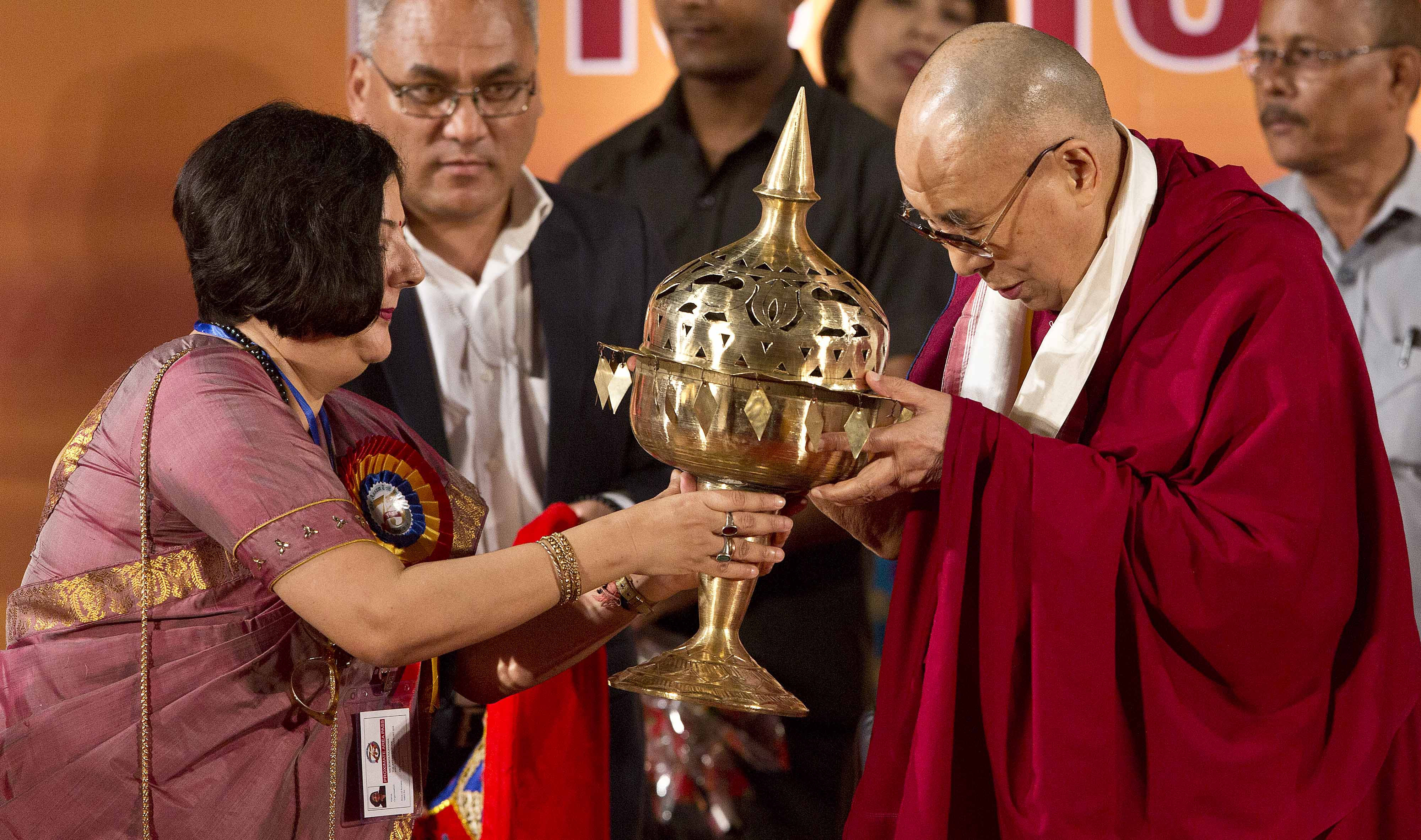 """Babita Rajkhowa, Director of Assam Tribune newspaper, presents a Sarai, a traditional Assamese brass handicraft, to Tibetan spiritual leader Dalai Lama during the platinum jubilee celebrations of Assam Tribune newspaper in Gauhati, India, Saturday, April 1, 2017. The Dalai Lama has recalled his 1959 flight to India from Tibet ahead of a visit to northeast India's Arunachal Pradesh state despite objections by China, which considers it a disputed region. Last month, China warned of """"severe damage"""" to relations with India and increased regional instability if the Dalai Lama proceeds with his April 4-11 trip to the state. (AP Photo/Anupam Nath)"""