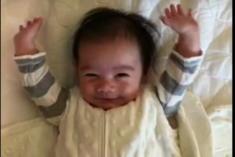 Adorable baby starts every day by throwing his hands into the air