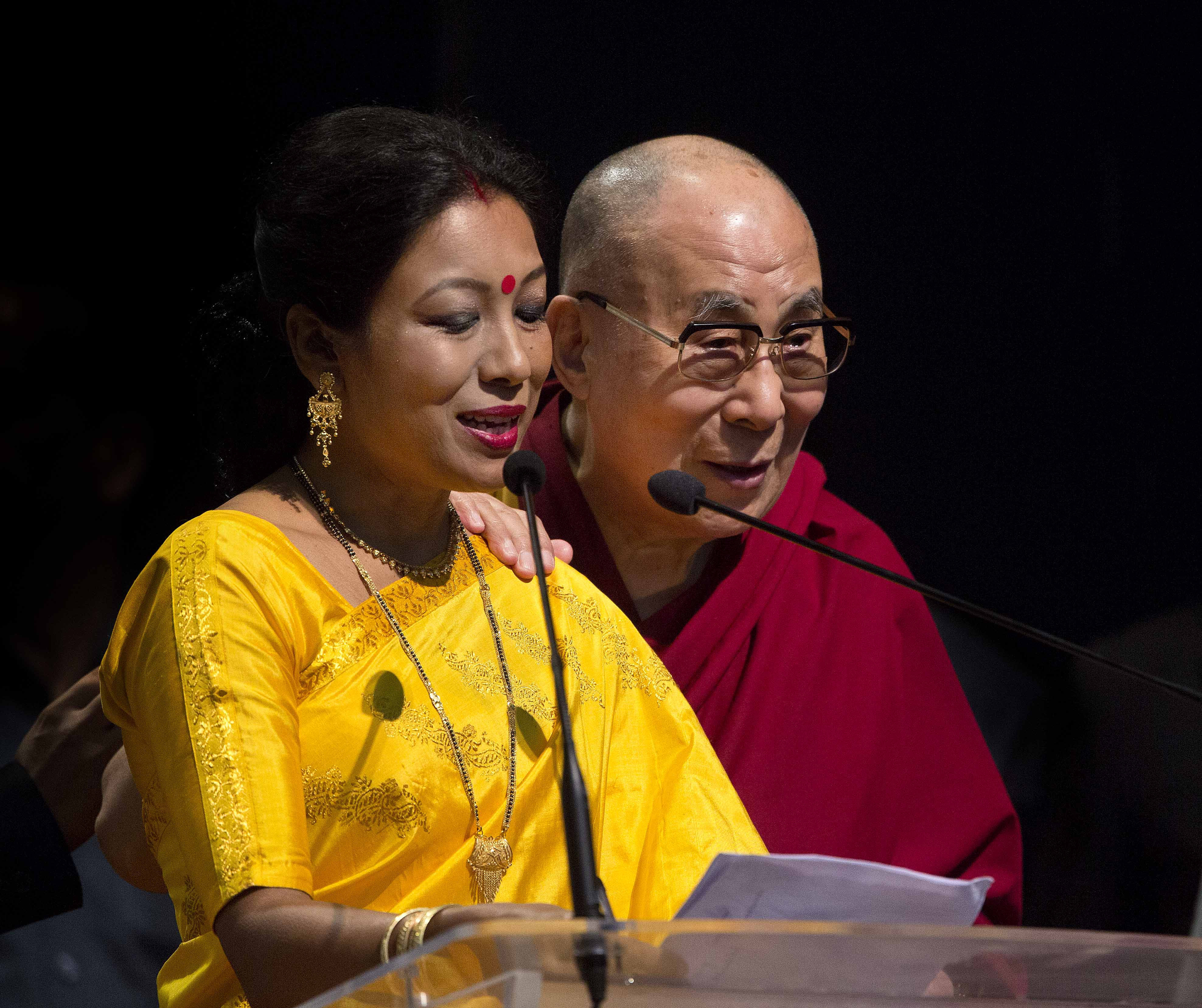 """Tibetan spiritual leader the Dalai Lama, right, listens to an Indian woman who was welcoming him prior to his lecture on """"Ancient Indian Knowledge in Modern Times"""" at the Gauhati university campus in Gauhati, north eastern Assam state, India, Sunday, April 2, 2017. (AP Photo/Anupam Nath)"""