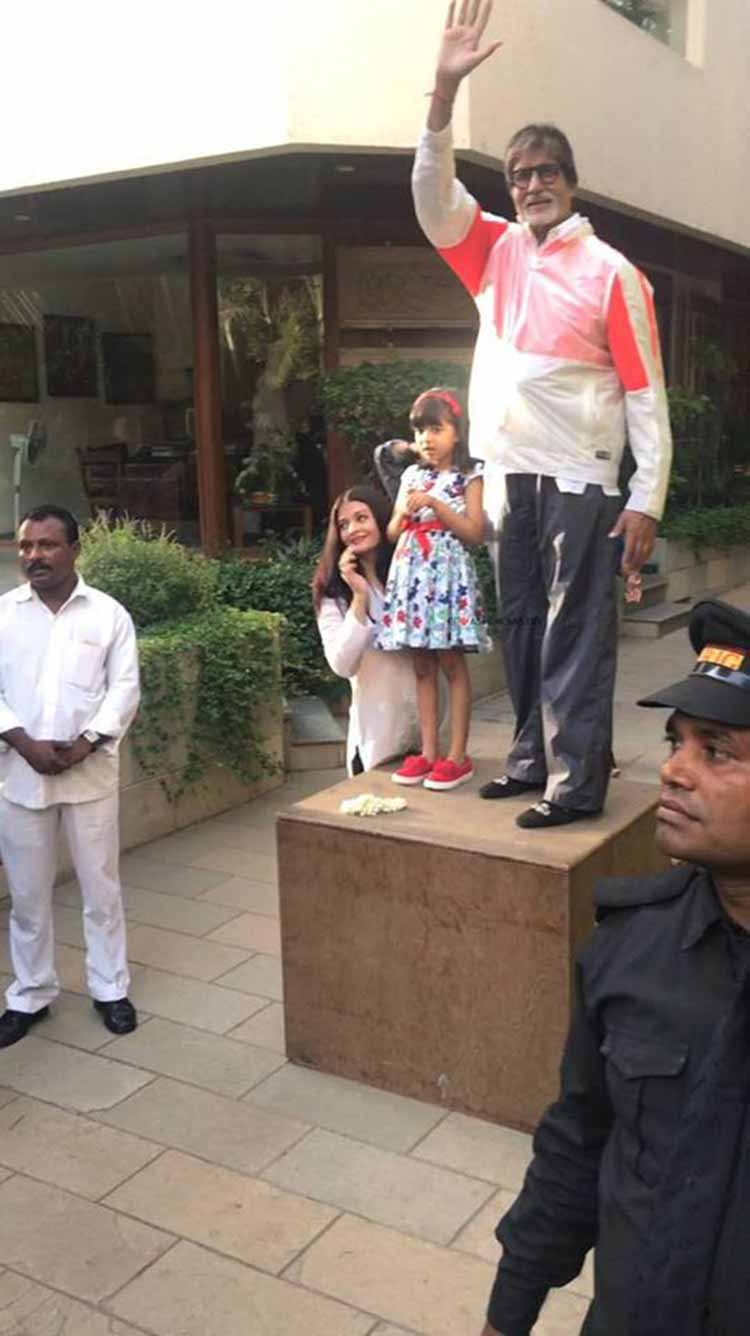 Amitabh Bachchan greeting his fans as Aaradhya looks by