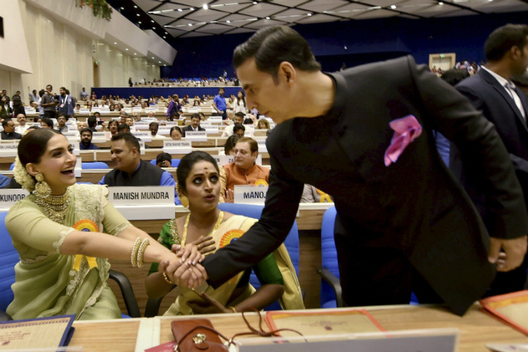 Akshay Kumar greets Sonam Kapoor at the 64th National Awards ceremony. (Courtesy: PTI photo)