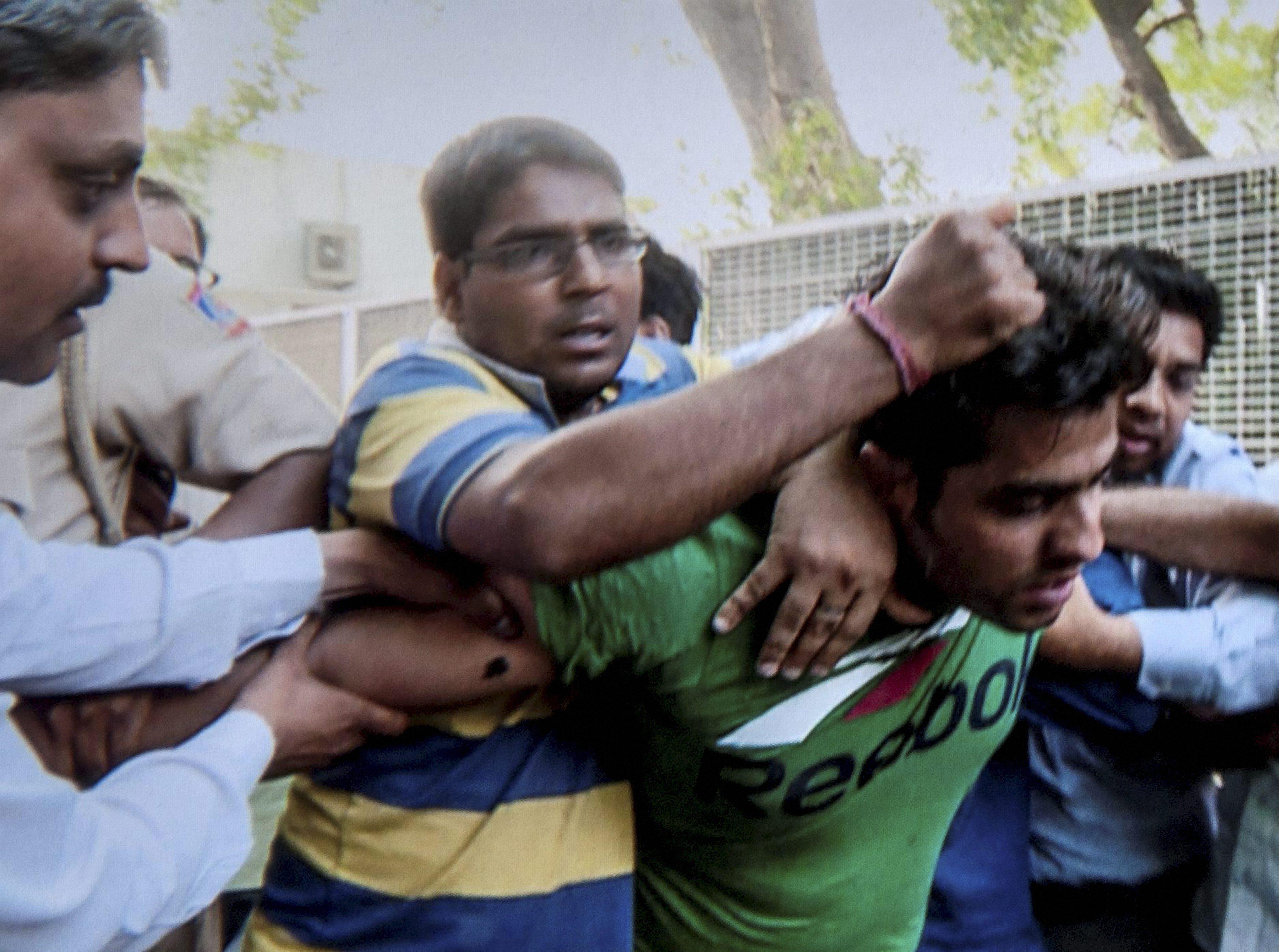New Delhi: Supporters of sacked AAP minister Kapil Mishra thrash Ankit Bhardwaj who attacked Mishra during his hunger strike, in New Delhi on Wednesday. PTI Photo (PTI5_10_2017_000293B)