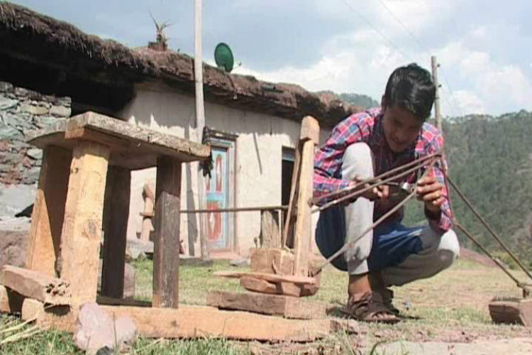 16-year-old Surjeet Singh checking the springs of his manually operated JCB-like machine
