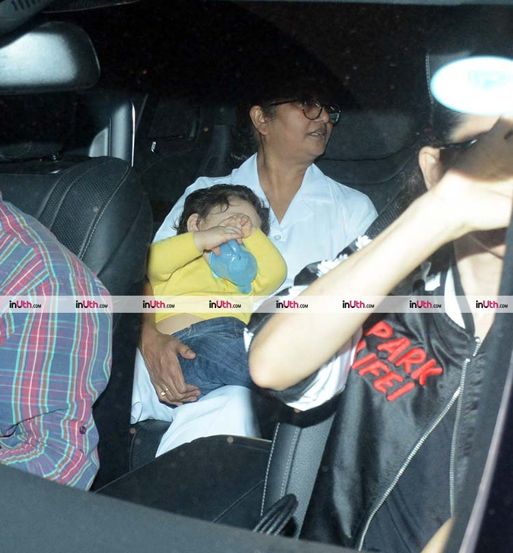 Taimur trying to hide his face from the shutterbugs
