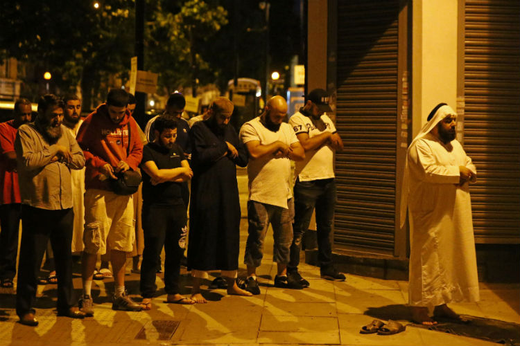 Men pray after a vehicle collided with pedestrians near a mosque in the Finsbury Park neighborhood of North London