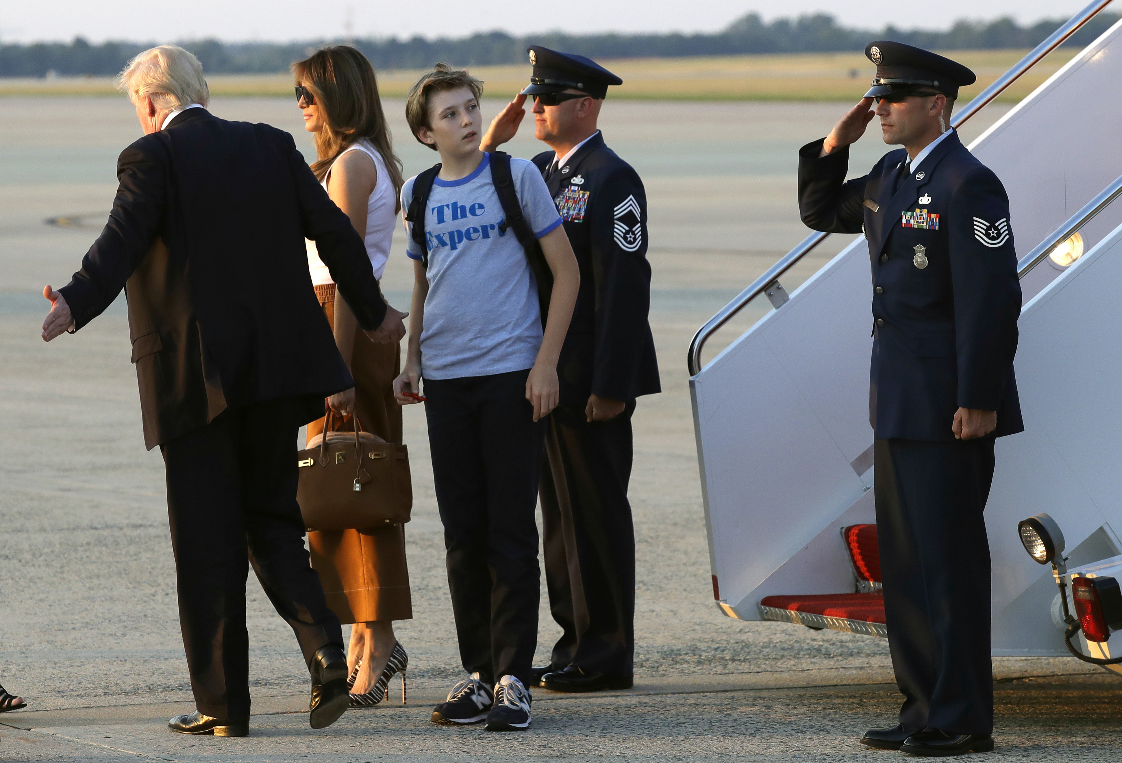 Barron Trump, son of President Donald Trump, looks back at Air Force One after arriving with President Trump, left, and first lady Melania Trump at Andrews Air Force Base, Md., Sunday, June 11, 2017. Trump is returning to Washington after spending the weekend at Trump National Golf Club in Bedminster, N.J. (AP Photo/Patrick Semansky)