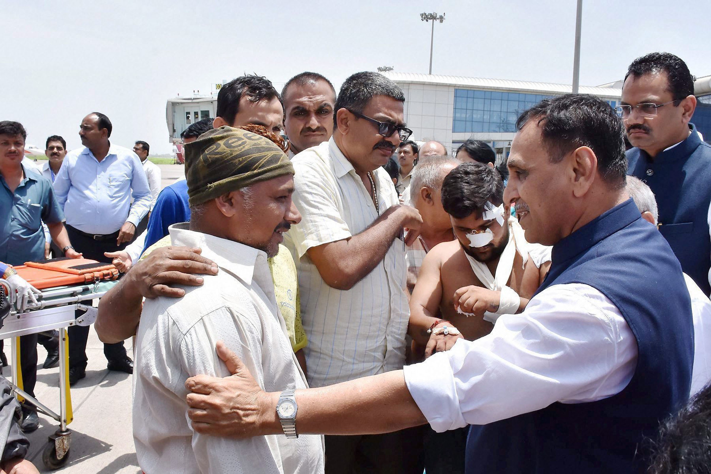 Surat: Gujarat Chief Minister Vijay Rupani meeting with the Amarnath pilgrims, injured in the terror attack in Jammu and Kashmir, after they were brought to the Surat airport in an IAF plane on Tuesday. PTI Photo
