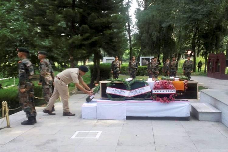 Poonch: A police officer laying a wreath at the coffin of Lance Naik Mohammed Naseer at a ceremony in Poonch on Sunday. PTI Photo