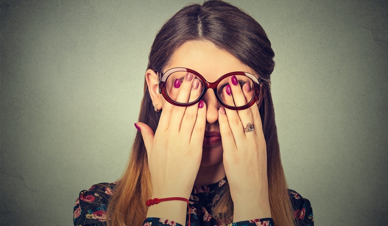Young woman in glasses covering face eyes with both hands