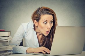 Shocked Woman Sitting In Front of Laptop