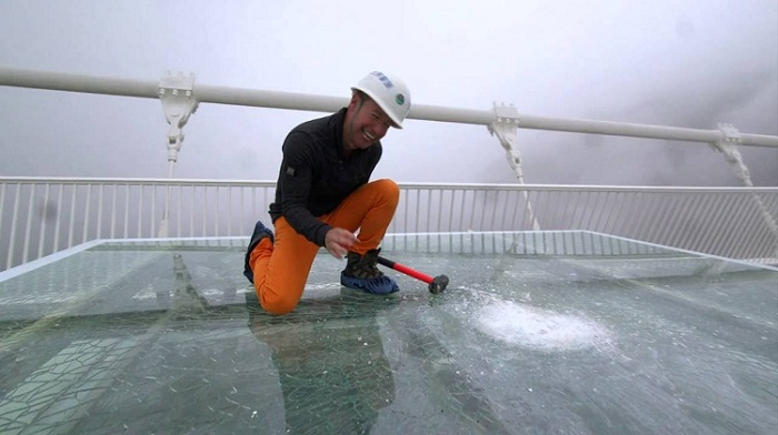 Chinese workers are checking safety of a glass bridge by smashing it withsledgehammers!