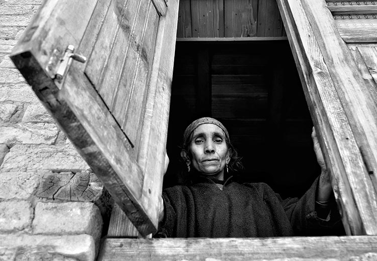 An elderly Kashmiri woman poses for the camera