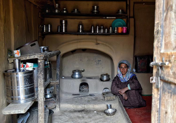 An elderly Kashmiri woman poses in the kitchen of her traditionally built house