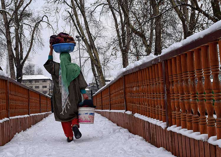 A woman working on her household chores in the snow-laden alleys