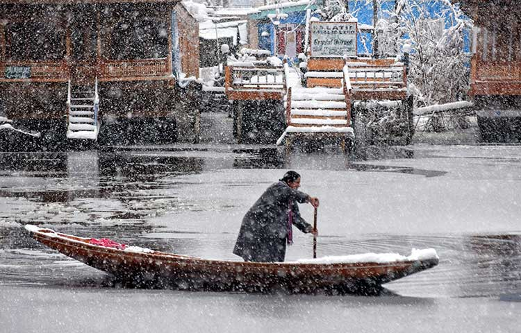 A woman rowing the boat in the Dal Lake amid snowfall