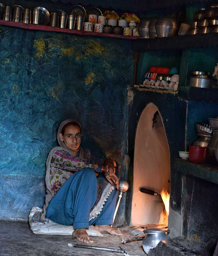 A Bakarwal woman inside the kitchen of her house