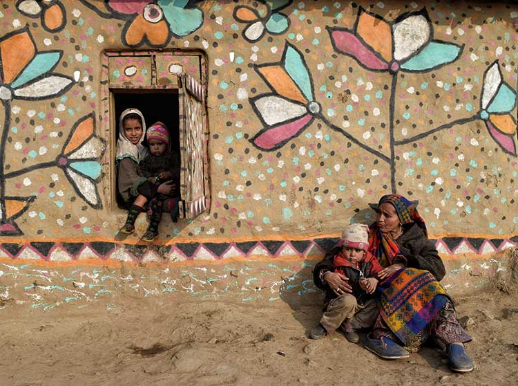 A Bakarwal woman sitting outside her house with children in Kashmir