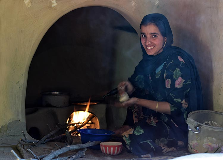 A Bakarwal woman poses for the camera as she cooks in a traditional kitchen