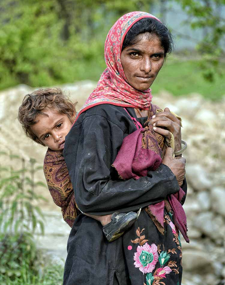 A Kashmiri Bakarwal woman poses with her child
